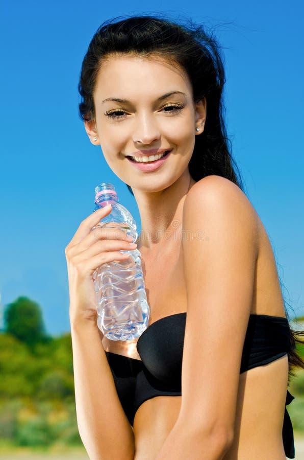 Mooi donkerbruin meisje dat een fles water houdt. stock foto