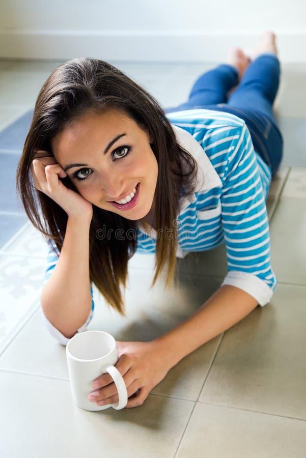 Mooi donkerbruin meisje dat op de vloer en het drinken c ligt royalty-vrije stock fotografie
