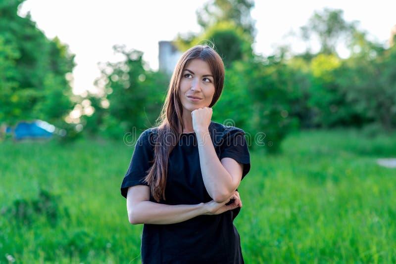 Mooi donkerbruin meisje in de zomer in een park in openlucht met een handengebaar die een nadenkende blik tonen Dromen van iets stock fotografie