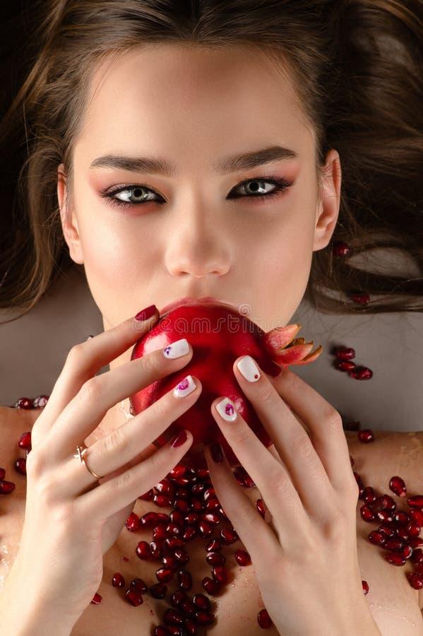 Mooi donkerbruin meisje die granaatappel, hierboven eten van stock foto's
