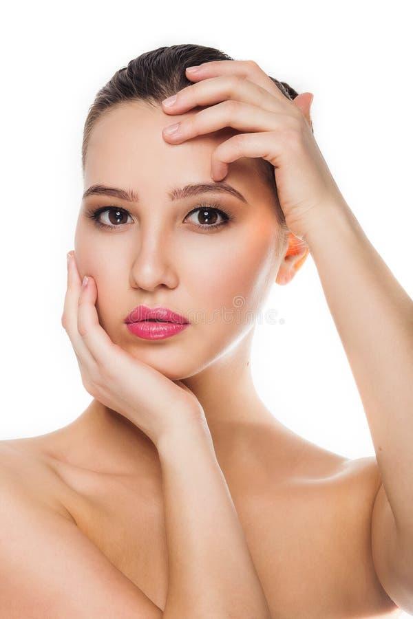 Mooi donkerbruin meisje die met schone, gezonde huid, make-up, zachte handen haar hoofd met de twee partijen houden die de camera stock foto