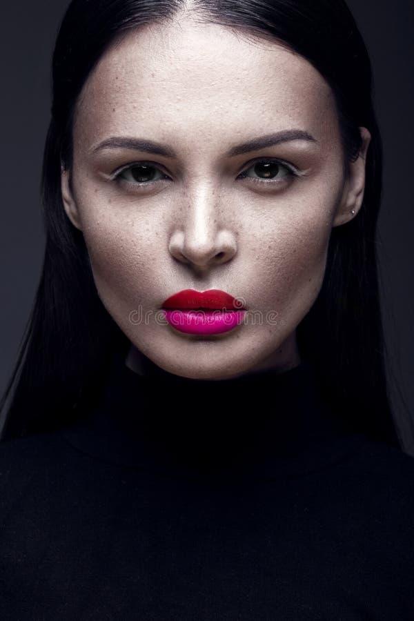 Mooi donkerbruin meisje in een zwarte kleding, een recht haar en een in make-up Het gezicht van de glamourschoonheid royalty-vrije stock fotografie