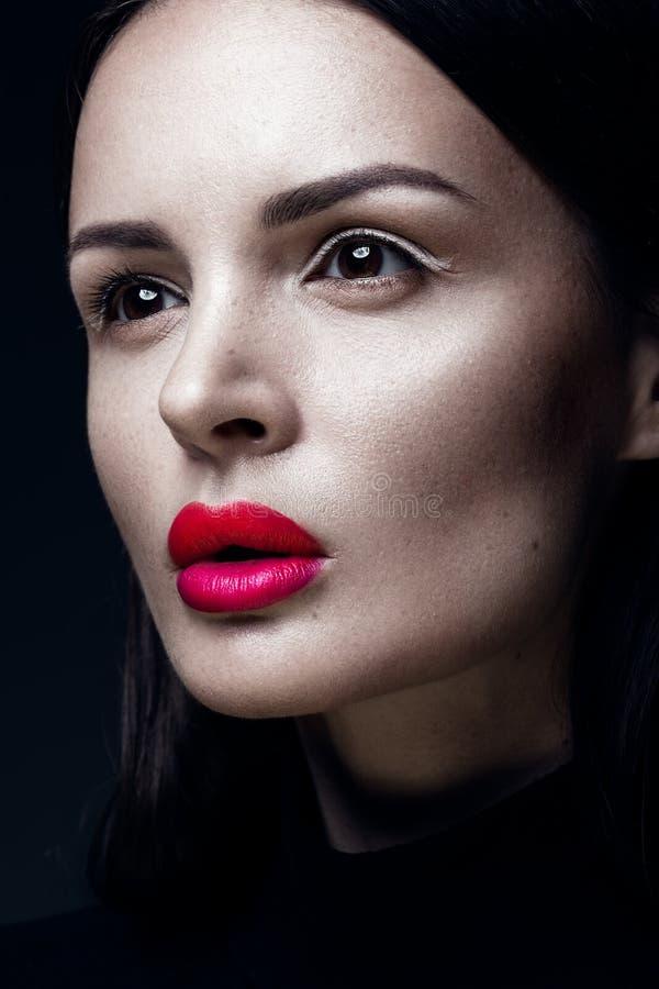 Mooi donkerbruin meisje in een zwarte kleding, een recht haar en een in make-up Het gezicht van de glamourschoonheid stock foto