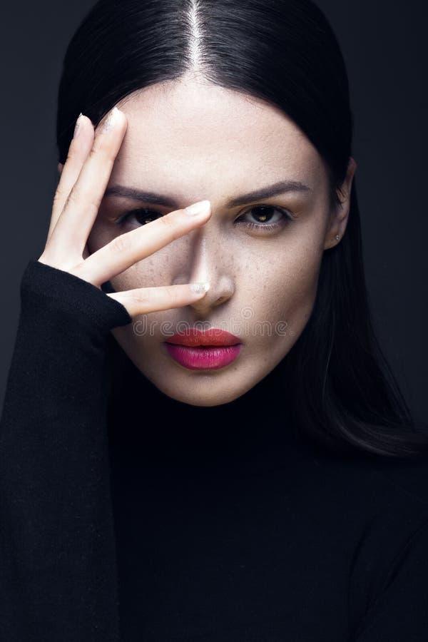 Mooi donkerbruin meisje in een zwarte kleding, een recht haar en een in make-up Het gezicht van de glamourschoonheid stock fotografie