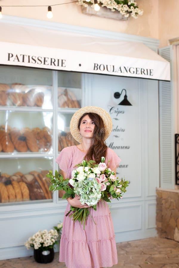 Mooi donkerbruin meisje met boeket van bloemen Een jonge vrouw bevindt zich dichtbij het venster van de bakkerijwinkel in een kle stock fotografie