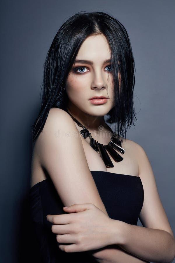 Mooi donkerbruin meisje met grote blauwe ogenoorringen en halsband royalty-vrije stock foto's