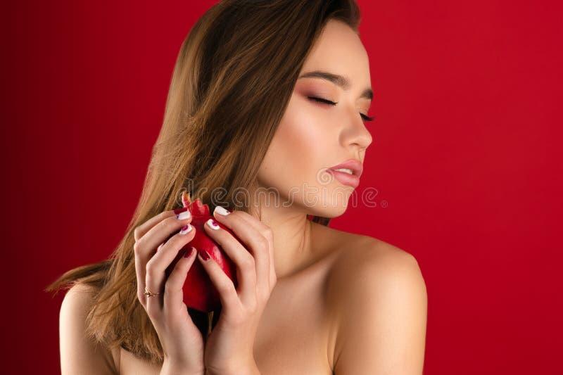 Mooi donkerbruin meisje met heldere make-up met granaatappel stock foto's