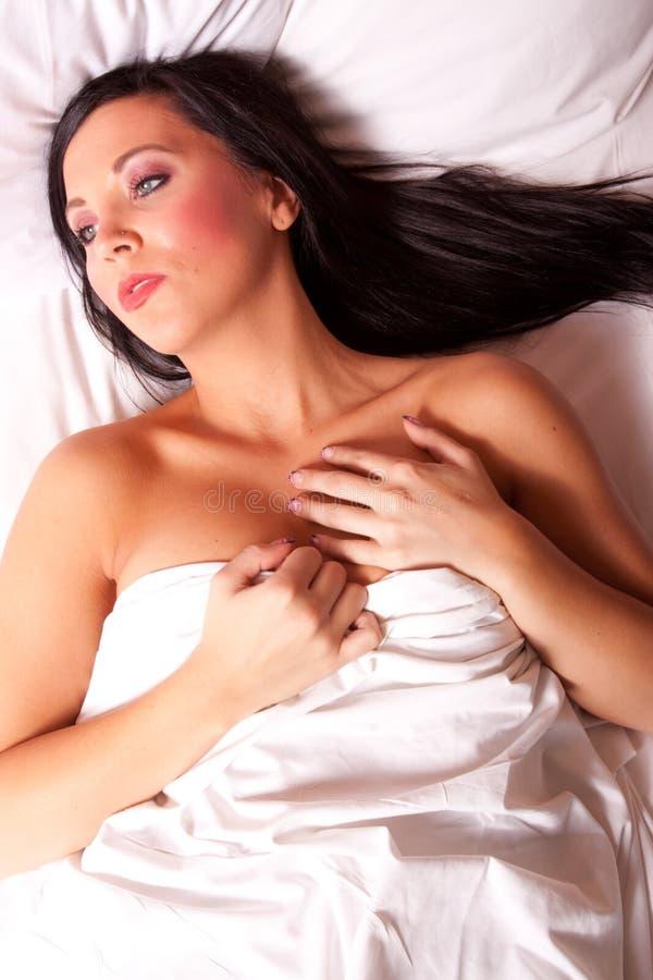 Mooi donkerbruin meisje op het bed stock afbeeldingen