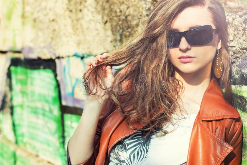 Mooi donkerbruin meisje in zonnebril die zich rond de muren met graffiti bevinden royalty-vrije stock foto's