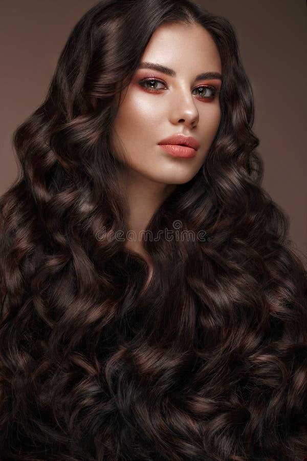 Mooi donkerbruin model: krullen, klassieke make-up en volledige lippen Het schoonheidsgezicht stock foto