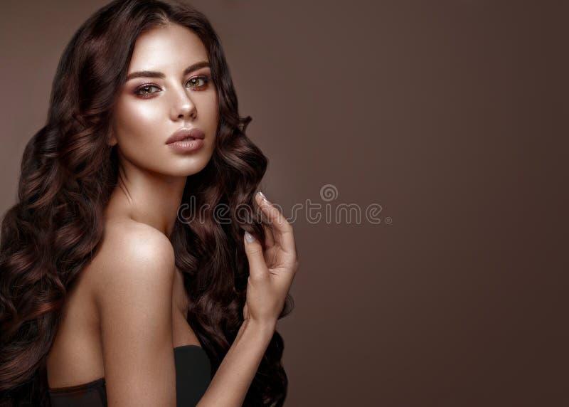 Mooi donkerbruin model: krullen, klassieke make-up en volledige lippen Het schoonheidsgezicht royalty-vrije stock afbeelding