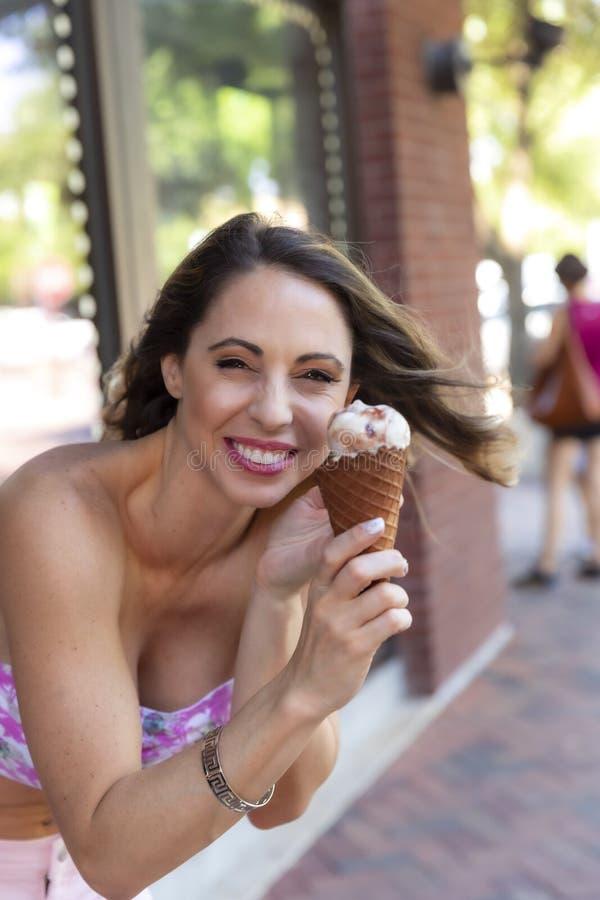 Mooi Donkerbruin Modeleats ice cream buiten een Roomijsopslag stock afbeelding
