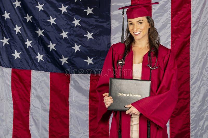 Mooi Donkerbruin Modelposing with een Diploma met een Amerikaanse Vlag op de Achtergrond stock foto