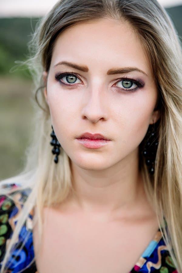 Mooi dromerig blondemeisje met blauwe ogen in een lichte turkooise kleding die op de stenen liggen stock afbeelding