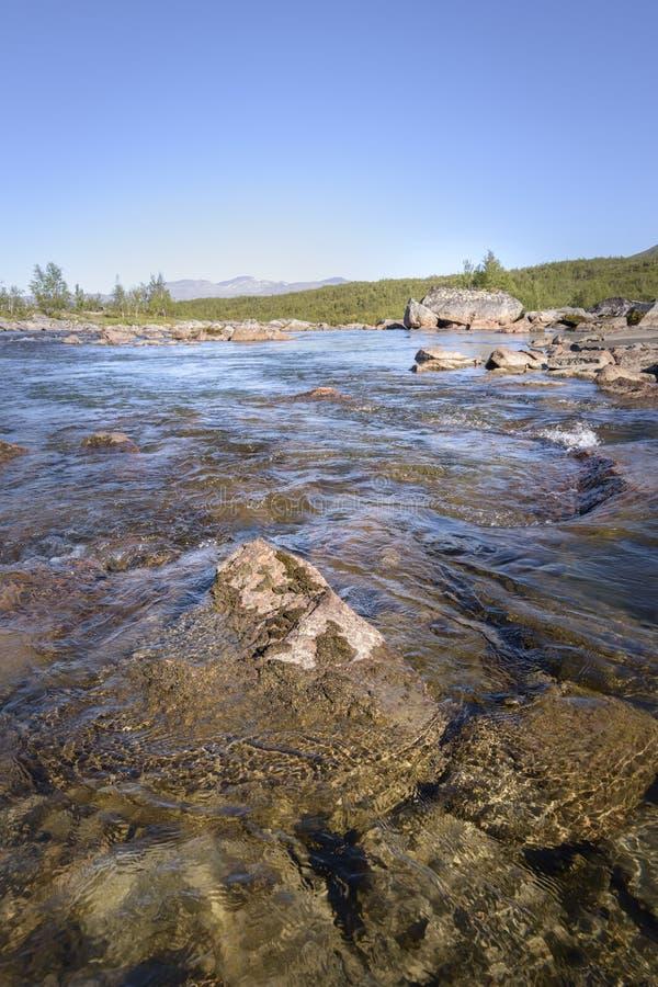 Mooi duidelijk en transparant water die de rotsen in de rivier met rustige blauwe hemelachtergrond tonen stock afbeelding