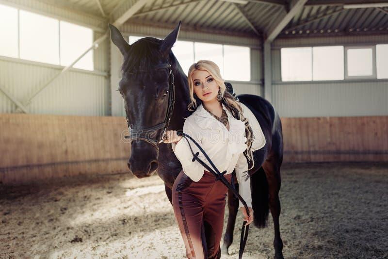 Mooi elegant jong blondemeisje die zich dichtbij haar paard bevinden die de eenvormige concurrentie kleden royalty-vrije stock fotografie