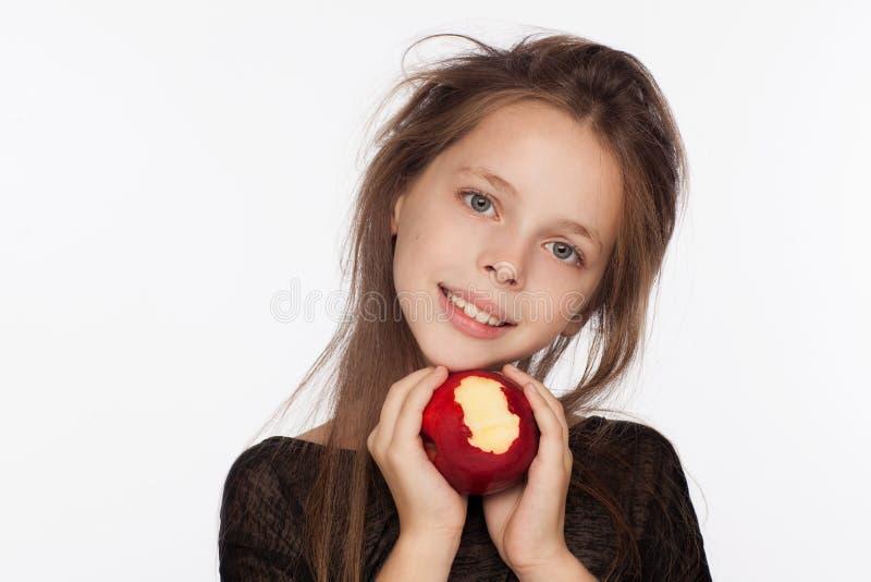 Mooi emotioneel acht-jaar-oud meisje met een appel Fotozitting in de studio Het meisje draagt een zwarte blouse royalty-vrije stock afbeeldingen