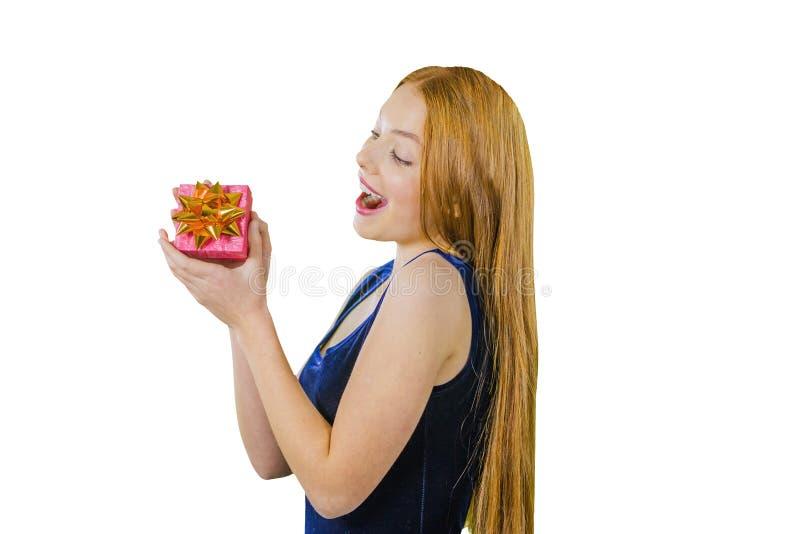 Mooi en blij roodharig meisje in blauwe kleding met een gift in haar handen voor Kerstmis op een geïsoleerde achtergrond royalty-vrije stock foto