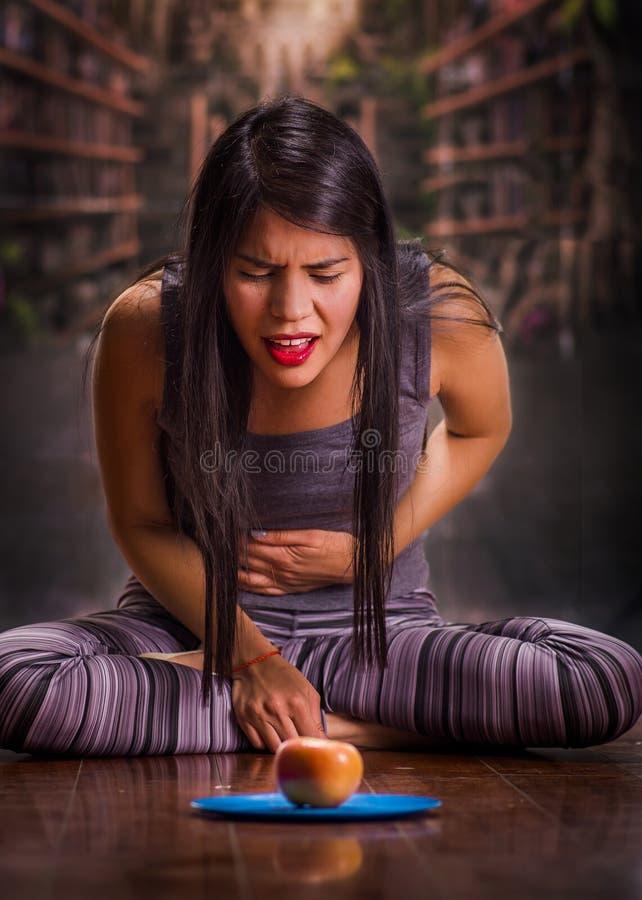 Mooi en eenzaam meisje die aan anorexy lijden, lijdend aan pijn in zijn maag wanneer zij een appel over een blauw kijkt royalty-vrije stock fotografie