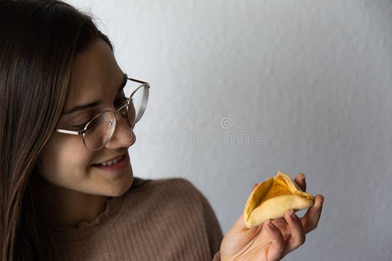 Mooi en gelukkig vrouwenportret dat hamantash Purim-abrikozenkoekje eet stock afbeeldingen