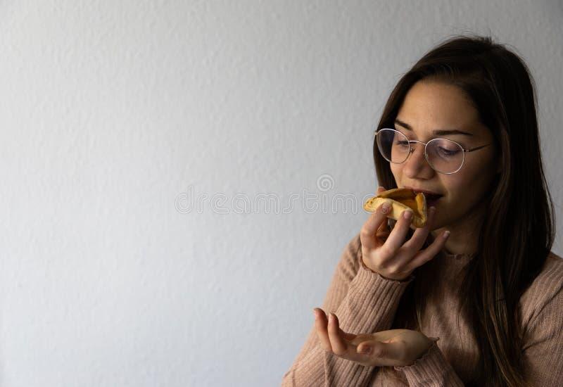 Mooi en gelukkig vrouwenportret dat hamantash Purim-abrikozenkoekje eet stock foto's