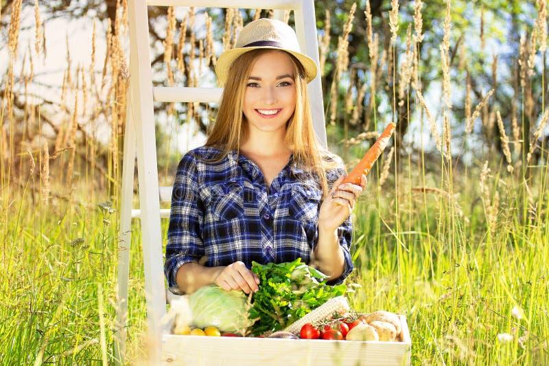 Mooi en jong meisje in hoed, met houten dooshoogtepunt van groenten en het houden van wortel in haar hand De zomeroogst stock afbeelding