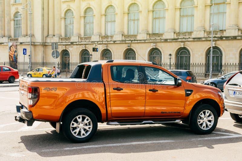 Mooi en krachtig oranje Ford Ranger T6 Wildtrack met codenaam die in centrum van Boekarest wordt geparkeerd stock foto