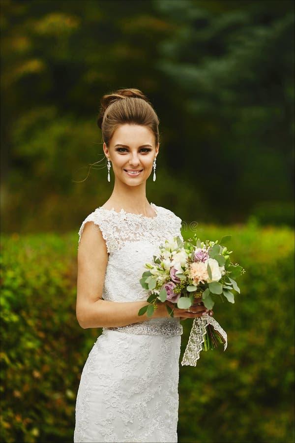 Mooi en modieus donkerbruin modelmeisje met heldere samenstelling en met huwelijks binnen kapsel, jonge modieuze bruid stock afbeelding
