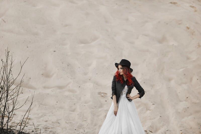 Mooi en modieus roodharig modelmeisje in het leerjasje, in de zwarte hoed en in modieuze huwelijkskleding royalty-vrije stock foto