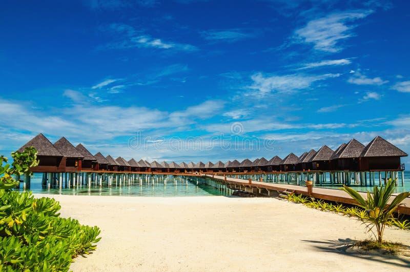 Mooi exotisch strand en houten brug aan verbazende exotische bungalowwen op turkoois water royalty-vrije stock fotografie