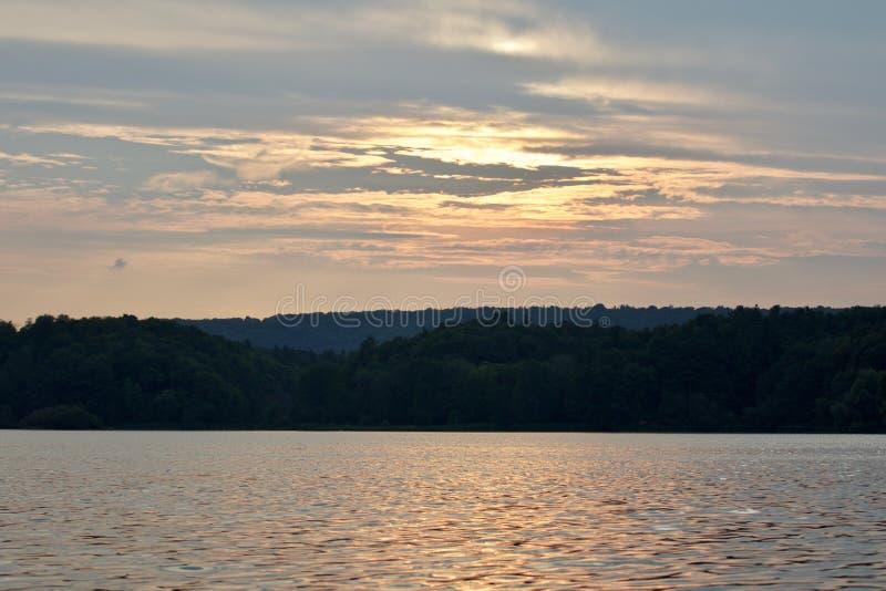 Mooi geïsoleerd beeld met het meer en het bos op de zonsondergang stock fotografie