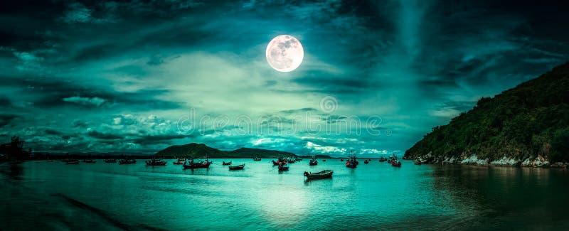 Mooi geheimzinnig aardlandschap Strand door het overzees met bergen en volle maan bij nacht stock foto's