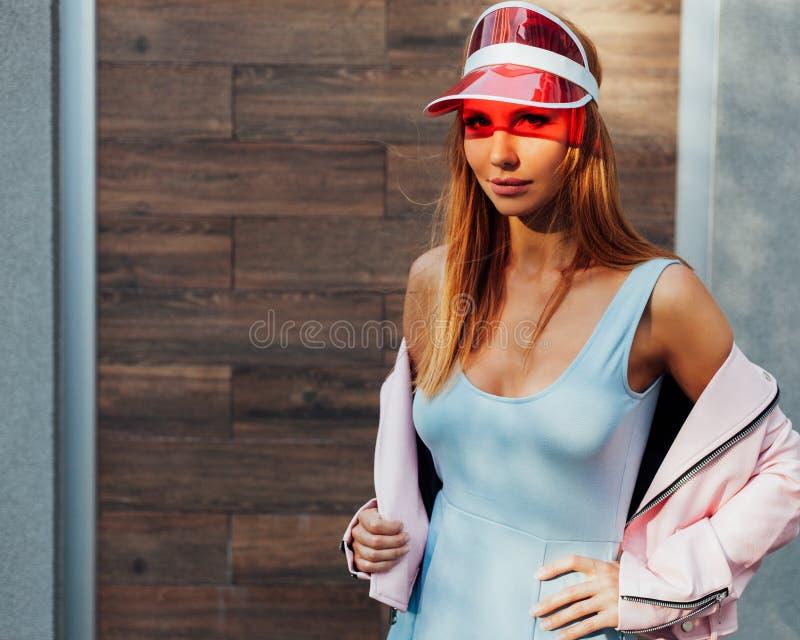 Mooi gelooid roodharigemeisje Stellen openlucht in modieuze blauwe kleding en roze jasje Zonnig portret van een Langharige jonge  stock afbeeldingen