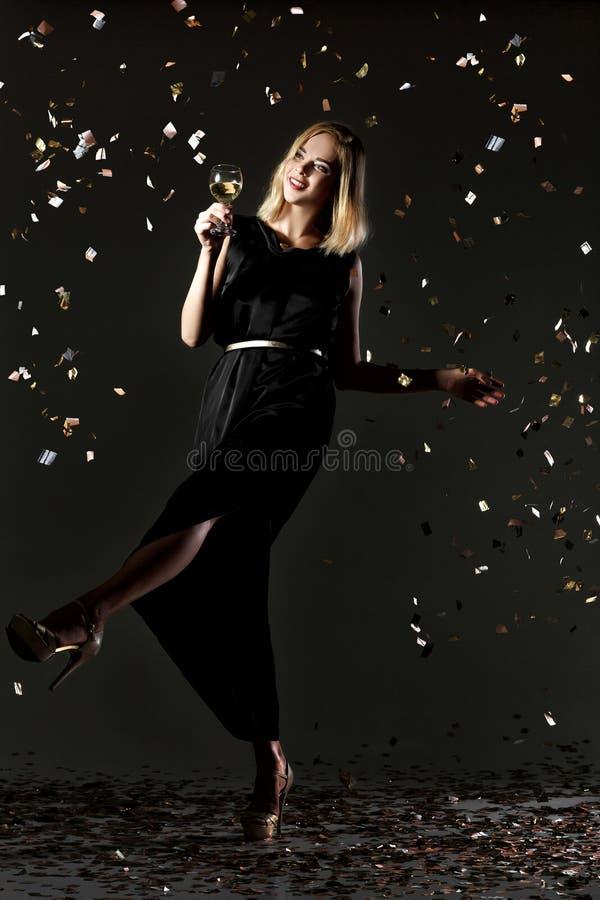Mooi gelukkig de holdingsglas van de blondevrouw witte wijn op zwarte achtergrond met confettien stock foto