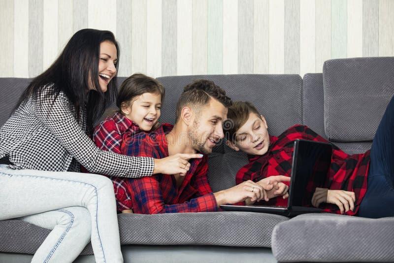Mooi gelukkig familieportret die thuis samen op bank zitten royalty-vrije stock foto