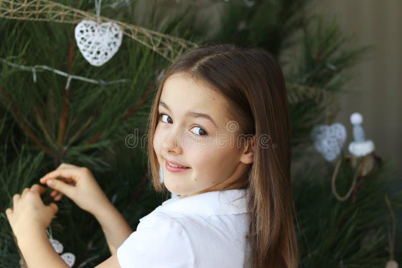 Mooi gelukkig glimlachend meisje die Kerstboom met witte decoratie verfraaien royalty-vrije stock fotografie