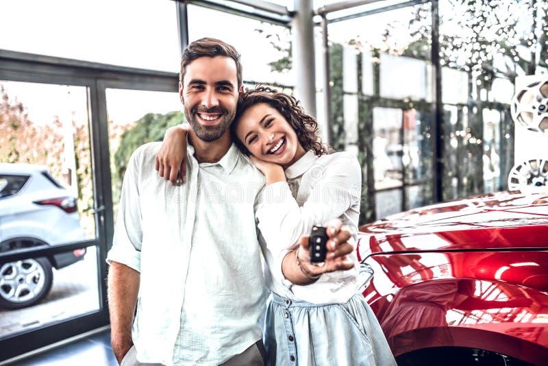Mooi gelukkig jong paar die houdend de sleutels aan hun nieuwe auto die vreugdevol bij het handel drijven glimlachen koesteren stock afbeeldingen