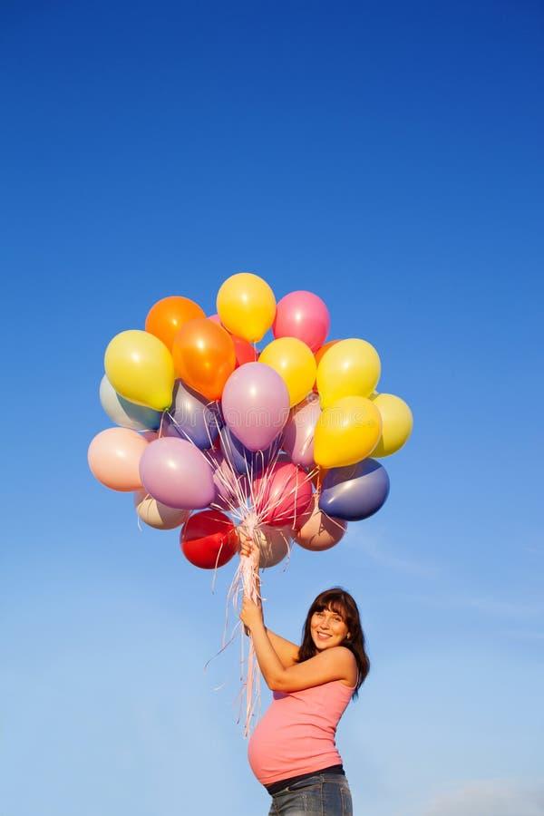 Mooi gelukkig jong zwanger vrouwenmeisje in openlucht met ballons stock fotografie