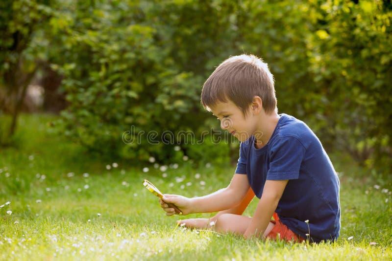 Mooi gelukkig kind, jongen, die aard met het overdrijven gla onderzoeken royalty-vrije stock foto