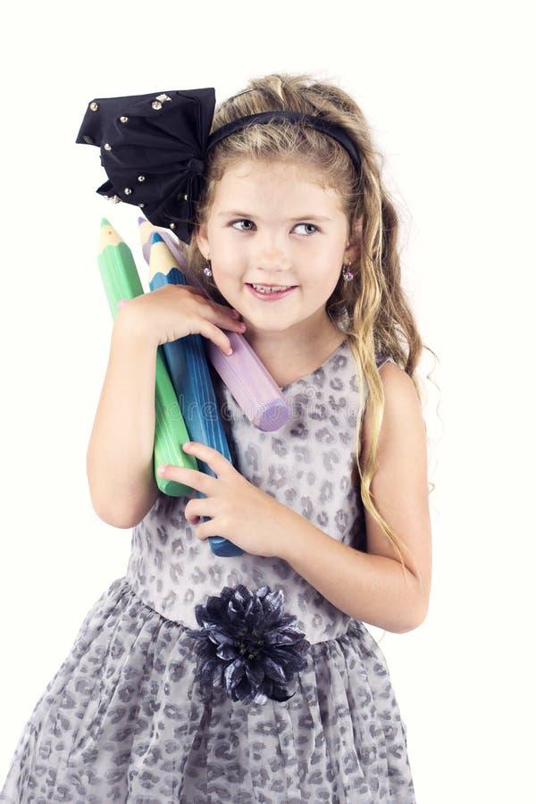 Mooi gelukkig meisje die grote kleurpotloden dragen royalty-vrije stock afbeeldingen
