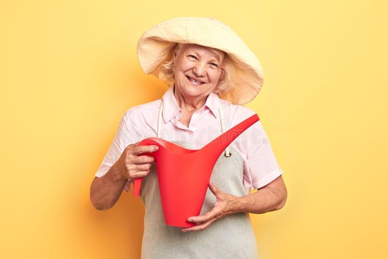 Mooi gelukkig meisje in grijze schort en de gele gieter van de hoedenholding stock foto's