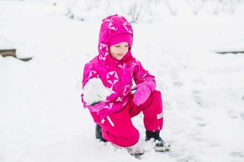 Mooi gelukkig meisje in het roze de winterkleren spelen royalty-vrije stock foto's
