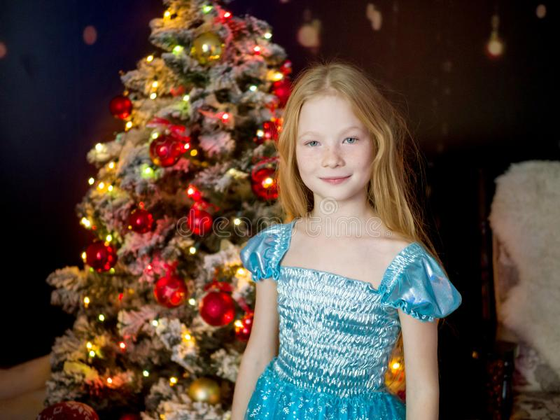 Mooi gelukkig meisje 10 jaar oud in de nieuwe jaarvakantie op de achtergrond van de Kerstboom in de lichten en royalty-vrije stock foto's