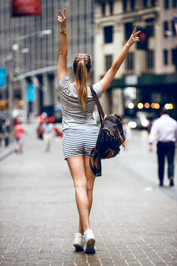 Mooi gelukkig meisje met een rugzakzak die op stadsstraat lopen en pret hebben De hand die van de vrouwengang omhoog de uitrustin stock foto's