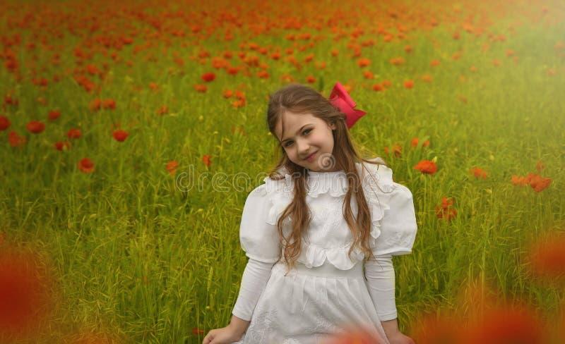 Mooi Gelukkig meisje in witte kleding die zich op papavergebied bevinden royalty-vrije stock fotografie