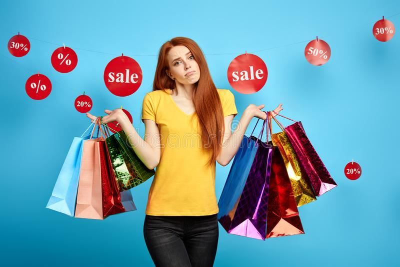 Mooi gembermeisje die met het winkelen zakken haar schouders ophalen, die twijfels hebben stock afbeeldingen