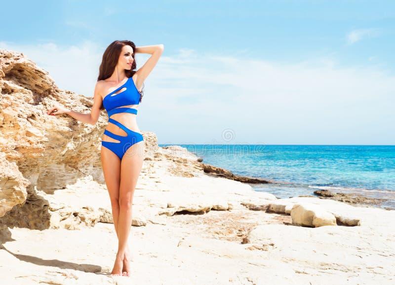Mooi, geschikt en sexy meisje in het blauwe zwempak stellen op een strand bij de zomer royalty-vrije stock foto's