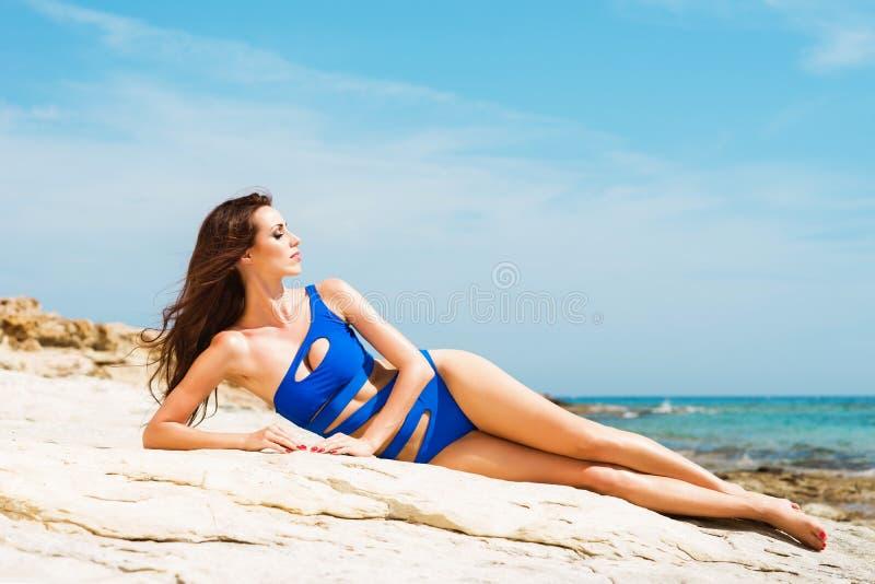 Mooi, geschikt en sexy meisje in het blauwe zwempak stellen op een strand bij de zomer royalty-vrije stock afbeelding