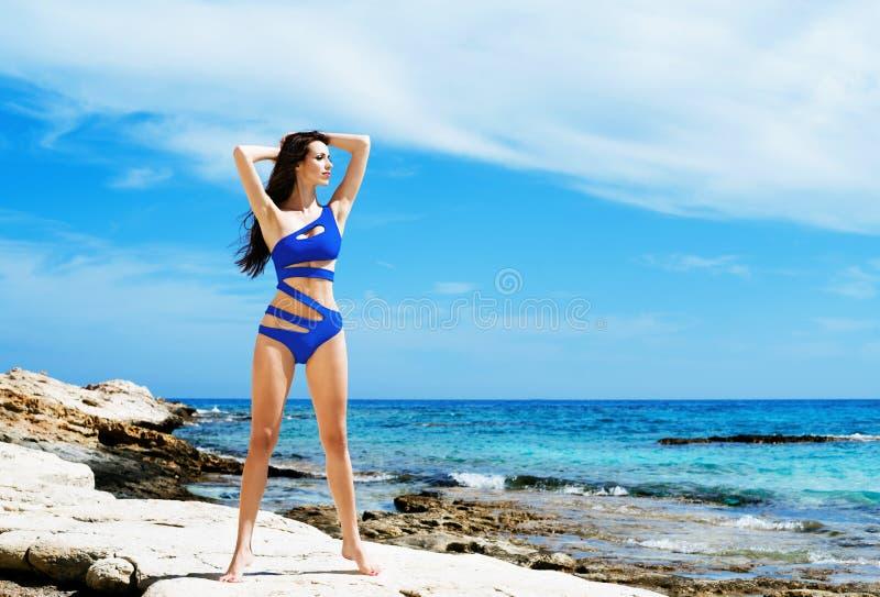 Mooi, geschikt en sexy meisje in het blauwe zwempak stellen op een strand bij de zomer stock afbeelding