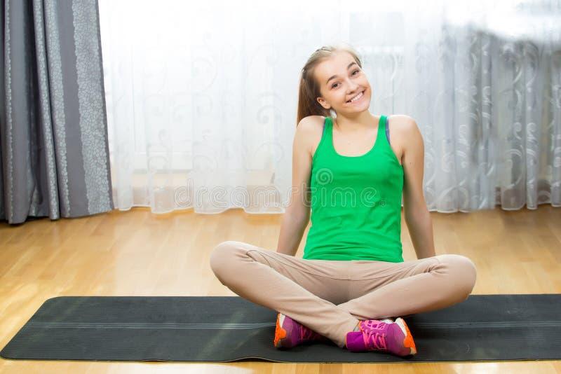 Mooi geschikt wijfje die op yogamat rusten na opleiding stock foto